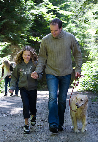 Father walking with daughter and dog